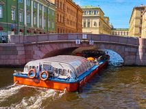 Boat with tourists under the Second Winter Bridge in Saint Petersburg, Russia. St. Petersburg, Russia - August 8, 2017: Boat with tourists, floating under the Royalty Free Stock Images