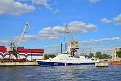 A coast guard cutter and the cranes on the embankment of Neva ri. ST.PETERSBURG, RUSSIA - AUGUST 09, 2017:  A coast guard cutter and the cranes on the embankment Stock Image