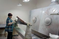 Worker varnishing the harp Stock Images