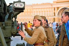 Girls in uniform induce anti-aircraft gun on the Palace square. ST.PETERSBURG, RUSSIA - AUGUST 08, 2017:  Girls in uniform induce anti-aircraft gun on the Palace Stock Image