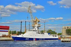 The Russian coast guard cutter and the cranes on the embankment. ST.PETERSBURG, RUSSIA - AUGUST 09, 2017:  The Russian coast guard cutter and the cranes on the Royalty Free Stock Images