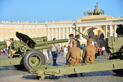 The soldiers sitting on the carriage of a cannon on the Palace s Stock Photos