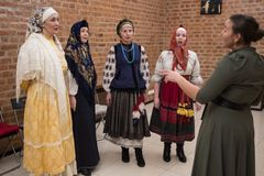 Female choral singing. St. Petersburg, Russia - December 17, 2017: A small group of middle-aged women in national costumes is taught singing with the help of a Royalty Free Stock Image