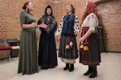 Female choral singing. St. Petersburg, Russia - December 17, 2017: A small group of middle-aged women in national costumes is taught singing with the help of a Stock Photography