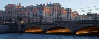 Anichkov bridge and Belosselsky-Belozersky Palace in St. Petersburg. St. Petersburg, Russia - December 27, 2015: Traffic on the Anichkov bridge against the Royalty Free Stock Photo