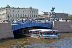 ST. PETERSBURG, RUSSIA. The excursion ship passes under Blue Bridge through the Moika River. ST. PETERSBURG, RUSSIA - JULY 11, 2016: The excursion ship passes Royalty Free Stock Photo
