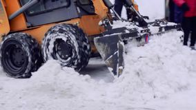St-Petersburg, Russia, 08 feb 2019-The service company cleans the yard of the house and the pavements from the snow and ice. Bobcat or a skid loader snow stock video footage