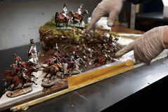 Creating the diorama with tin soldiers. St. Petersburg, Russia - February 21, 2017: Master creates the diorama using the tin soldiers in the workshop of Niena Royalty Free Stock Image