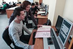 Students of Electrotechnical College in class in the laboratory. St. Petersburg, Russia - February 16, 2012: The teacher checks the accuracy of the assignment by royalty free stock image