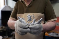 Tin soldier taken out from the casting form. St. Petersburg, Russia - February 21, 2017: Worker demonstrating the tin soldiers taken out from the casting form Royalty Free Stock Image