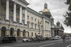 St.-Petersburg, Russia. St. Isaac`s Cathedral , horses with carriages where tourists sit. Horse carriage, a carriage traveling along the road along the yellow Stock Image