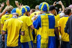 Backs of Swedish football fans supporters. St. Petersburg, Russia - July 3, 2018: Backs of Swedish football fans supporting Sweden national football team, going stock photo