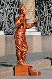 Living statue. ST PETERSBURG, RUSSIA - July 14, 2016: Bronze painted artist on a city street, living statues is the entertainment for passerby Stock Image