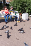 ST PETERSBURG, RUSSIA-JULY 04: Chłopiec karmi gołębie na ulicie Zdjęcie Stock