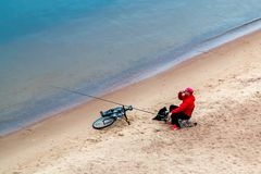 St. Petersburg, Russia - July 10, 2018: fisherman are fishing on the sandy shores of the Gulf of Finland under the bridge royalty free stock photo