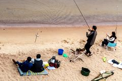 St. Petersburg, Russia - July 10, 2018: Group of fishermen are fishing on the sandy shores of the Gulf of Finland under the bridge royalty free stock photography