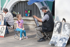 ST.PETERSBURG,RUSSIA-JULY 04:the sidewalk artist draws portraits Royalty Free Stock Photo