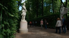 Tourists walk near an antique statues in the Summer Garden Royalty Free Stock Photography