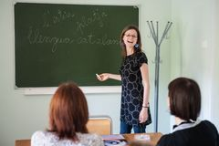 Spanish teacher, young attractive girl at the blackboard explains the learning material to stock photos