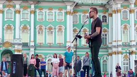 ST. PETERSBURG, RUSSIA - june 26, 2019: Street guitar musician perform for tourists and tips on city center. Palace Square at summer. People watching and stock video footage