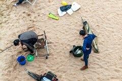 St Petersburg, Russia - 10 luglio 2018: Il gruppo di pescatori sta pescando sulle rive sabbiose del golfo di Finlandia sotto il p immagini stock libere da diritti