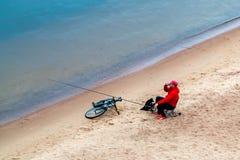 St Petersburg, Russia - 10 luglio 2018: il pescatore sta pescando sulle rive sabbiose del golfo di Finlandia sotto il ponte fotografia stock libera da diritti