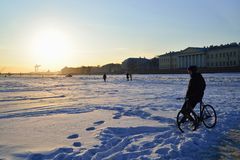 A man with a Bicycle stands on the ice of the Neva river and loo Royalty Free Stock Photography