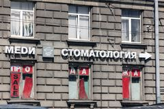 Advertising sign on the facade of the house: dentistry. St. Petersburg, Russia - May 04, 2019: advertising sign on the facade of the house: dentistry Russian stock image
