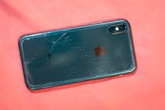 ST. PETERSBURG, RUSSIA - MAY 27, 2018: Black smartphone Iphone X broken glass on the back cover of the phone close up.  royalty free stock photography