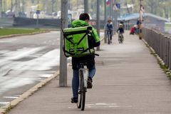 Courier of Delivery club delivers food on a bicycle. St. Petersburg, Russia - May 10, 2019: Delivery Club - Eats food delivery. Delivery courier rides a bicycle royalty free stock photo