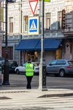 Female police officer at the crossroads. St. Petersburg, Russia - May 01, 2019: female police officer at the crossroads in a green vest with the abbreviation DPS stock photography