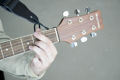 Man plays chords on Martinez guitar on gray background stock image