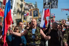 Eople hold flags and pictures of World War Two soldiers as they take part in the Immortal Regiment march. ST. PETERSBURG, RUSSIA - MAY 9, 2018: People hold flags royalty free stock photos