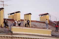 Tour by roofs in St. Petersburg, Russia. St. Petersburg, Russia - May 19, 2017: People make photo during the tour by roofs. Such tours is popular among young Stock Photo