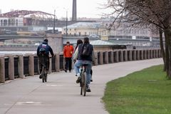 Cyclists on the waterfront. St. Petersburg, Russia - May 02, 2019: People ride bicycles along the Neva River Embankment. cyclists ride around the city stock image
