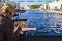 St. Petersburg, Russia - May 22, 2014: street artist paints river landscape on the bridge over the Neva River. Stock Images