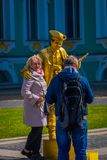 ST. PETERSBURG, RUSSIA, 01 MAY 2018: Unidentified couple close to golden paint mime artist or living golden statue royalty free stock images