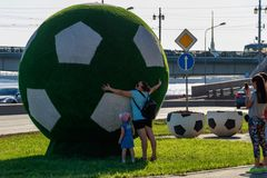 A female mother with a baby girl is hugging a huge green soccer ball. Tourists take pictures of her on a smartphone stock images