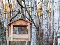 St. Petersburg, Russia - November 22, 2018:: Bird feeder in the shape of a house on a branch in the winter forest.  royalty free stock images