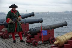 Cannoneer at retro cannons. St. Petersburg, Russia - October 27, 2016: Cannoneer in retro uniform at the cannons that will be installed on the first Russian ship royalty free stock image