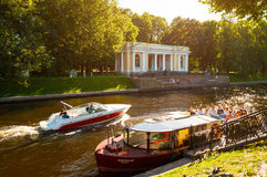 St Petersburg, Russia -Rossi Pavilion in the Michael Garden and the Moika river with pleasure boats Royalty Free Stock Photo