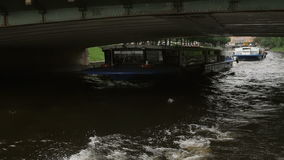 ST PETERSBURG, RUSSIA - 25 Sep 2016. River bus going under the bridge. People and buses on the bridge. slow mo. ST PETERSBURG, RUSSIA - 25 Sep 2016. Daytime view stock video footage