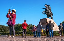 St. Petersburg, Russia - September 24, 2017: Tour group from China near the monument to the bronze Horseman. A woman makes a selfie with a monument Royalty Free Stock Images