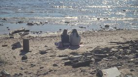 St-Petersburg, Russia. Two girls resting on dirty beach. Park Of The 300th Anniversary, Saint-Petersburg, Russia - July 4, 2018. Two girls are resting on a dirty stock video