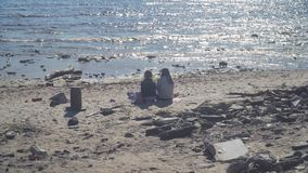 St-Petersburg, Russia. Two girls resting on dirty beach. Park Of The 300th Anniversary, Saint-Petersburg, Russia - July 4, 2018. Two girls are resting on a dirty stock footage