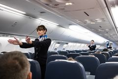 Safety briefing on board an aircraft. St. Petersburg, Russian Federation - October 16, 2017: Stewardesses in the cabin of the Boeing 737-800 passenger airplane royalty free stock image