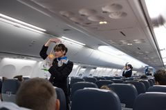 Safety briefing on board an aircraft. St. Petersburg, Russian Federation - October 16, 2017: Stewardesses in the cabin of the Boeing 737-800 passenger airplane stock photography