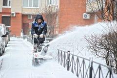 St. PETERSBURG, RUSSLAND - 12. JANUAR 2016: ein Mann entfernt Schnee herein Lizenzfreies Stockbild