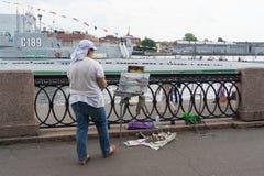 St Petersburg, Russland - 29. Juli 2017: ein Künstler auf dem Damm des Neva-Flusses zeichnet ein Segelboot lizenzfreie stockfotografie