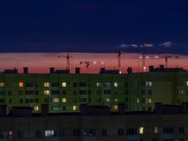 St Petersburg, Russland - 24. Juli 2018: Einige Baukräne auf dem Hintergrund des bunten Sonnenunterganghimmels stockfotografie